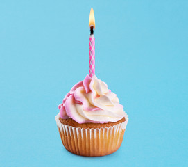 Cupcake with birthday candle on a blue background.