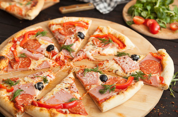 pizza, fresh pizza with mozzarella, tomatoes, ham and cheese. Italian pizzeria. Fresh pizza on the kitchen table