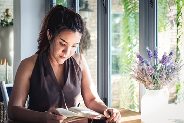 Comfortable of holiday, Young Asian beautiful woman sitting on table and reading interesting book in a cozy cafe