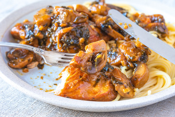 Italian cuisine - Marsala chicken with mushrooms and spaghetti on a plate, close-up, rustic style