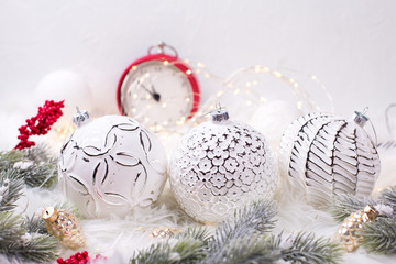 Three white balls, fir tree branches, red clock, red berries on white fur background.