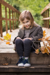 Adorable little girl is playing on an autumn background