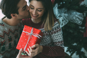 Young man kissing beloved woman on Christmas