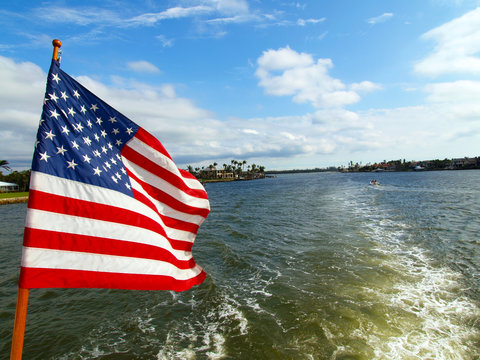 American flag on the boat waving, boat leaving waves behind