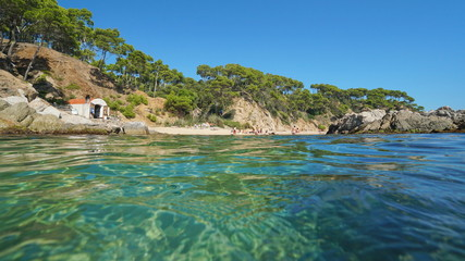 Spain Costa Brava beach with a fisherman hut near Palamos seen from water surface, Cala Estreta, Mediterranean sea, Catalonia