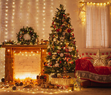 Christmas living room interior, decorated wood mantelpiece, lit up tree with red gold green baubles and ornaments, stars, wreath, candles, lightly toned, cosy chair with red cover, selective focus