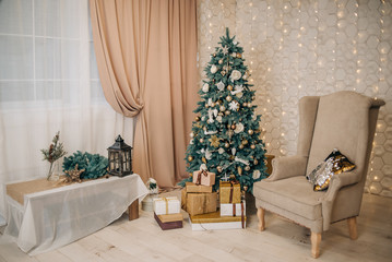 Stylish, calm festive, Christmas interior with a Christmas tree, gifts, an armchair. Beige and gold in the interior