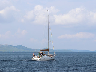 A sailing yacht is anchored in a bay. People bathe in the sea. Active rest on the Adriatic Sea of the Mediterranean region. Dalmatian riviera of Croatia. Prestigious and rich lifestyle