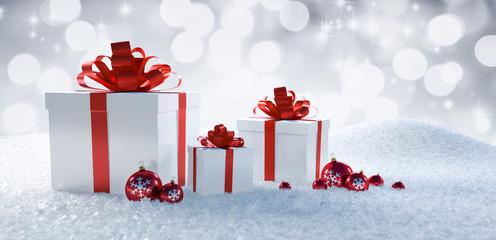 Weiße Geschenke mit rotem Band im Schnee
