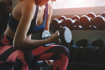 Young woman with a barbell, in a beautiful sports uniform.