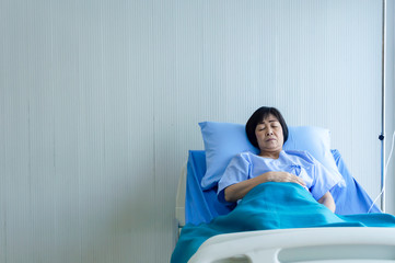 Older sick woman patient lay on bed in hospital with intravenous normal saline.
