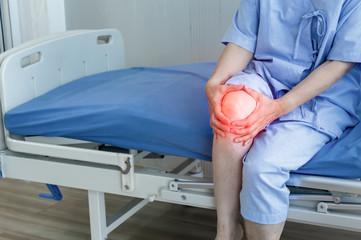 Elderly woman suffering from pain in knee.