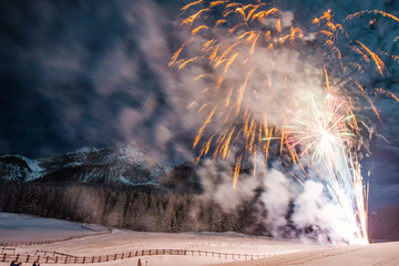 Firework for new year's eve in the mountains with some people whatching the explosions
