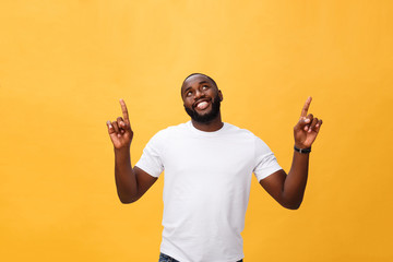 Young african american man over yellow background pointing upwards Wall mural