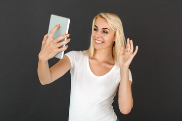 Freestyle. Woman standing isolated on black wall having video call on digital tablet waving to screen happy
