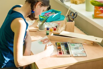 Teenage girl at home is engaged in creativity, drawing watercolor at a table in room. Child creativity, recreation, development