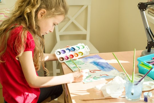 Little beautiful girl painting with watercolors, sitting at home at the table. Child creativity, recreation, development