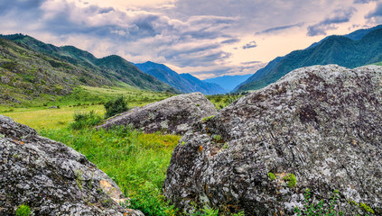Beautiful summer landscape in the mountain valley with scattered boulders