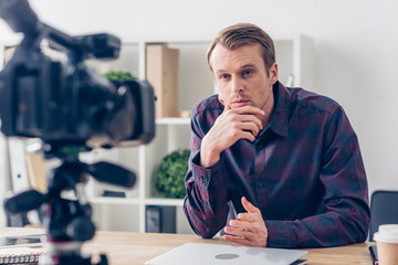 handsome pensive male video blogger recording vlog in office