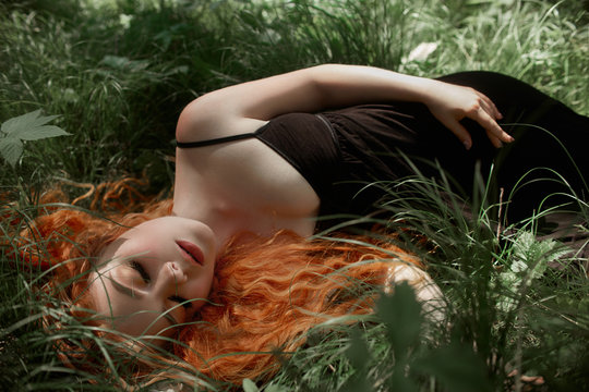 Romantic woman with red hair lying in the grass in the woods. A girl in a light black dress sleeps and dreams in a magical forest