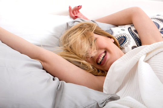 A beautiful happy young woman lying on a bed and covered with a white blanket.