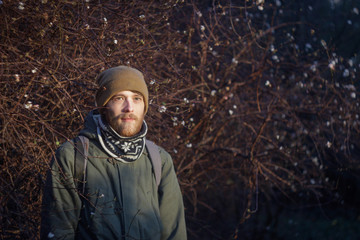 Young blond white man with a beard wearing a scarf, hat and backpack walking through the woods