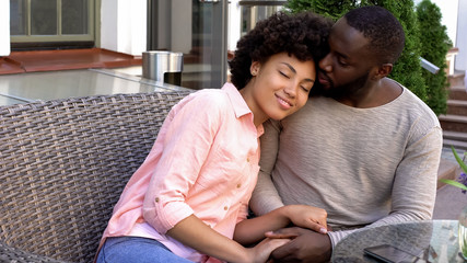 Loving afro-american couple on romantic date in cafe, newlyweds holding hands