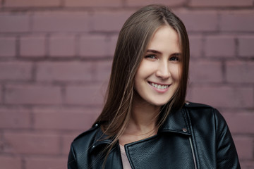 Young beautiful caucasian girl posing in a black leather jacket on a brick wall background.