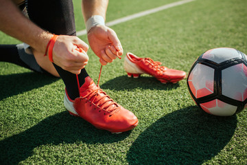 Picture of man lacing soccer sneaker on one leg. He stand on knee. Another sneaker is besides. Ball for game lying on lawn. Close up. Cut view.