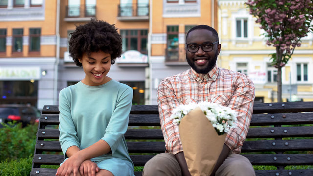 Embarrassed couple sitting on bench with flowers, first date, affection emotions
