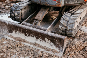 Close up of bulldozer working with soil on construction site