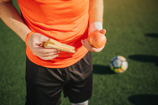 Close up of football plaueer holding apple and sandwich in hands. He stands alone. Ball lying on green lawn besides man. Sunny weather is outside.