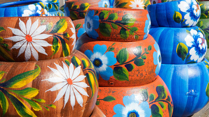 Close up on sets of colorful hand painted Mexican ceramic pots, traditional pottery found at a market stall in Old Town, a state historic park in San Diego, California, USA