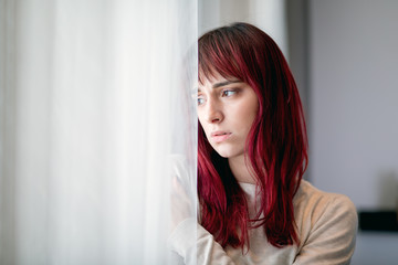 Depressed young woman near window at home thinking about unpleasant experiences Wall mural
