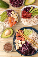 poke bowl Hawaiian food. a plate of rice, salmon, avocado, cabbage and cheese. next to sesame and fresh avocado on a natural wooden table top view.