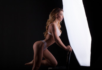 Young beautiful woman with perfect body posing in a studio in front of a lamp