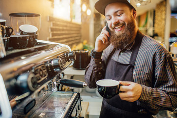 Nice bearded barista stands at coffee machine and talks on phone. He smiles. Guy hold cup of coffee in hands.