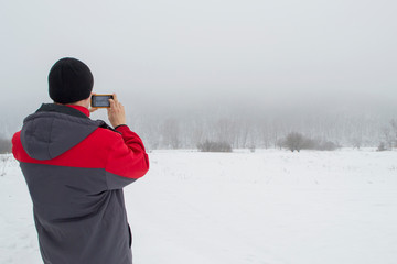 A man in a warm bright jacket stands back to the camera and photographs the winter snow-covered landscape. Enjoying northern beauty. Concept of winter idyll and harmony.