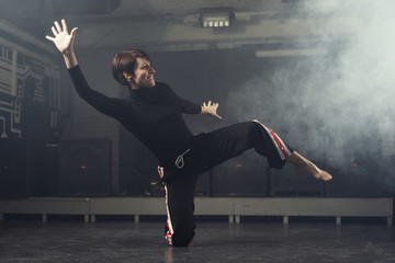 modern beautiful dancer in black clothes posing against the Studio in the smoke
