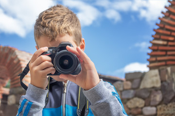Boy taking a picture with  digital camera. Photography, hobby and leisure concept