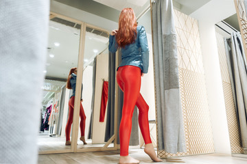 red-haired girl measures red leather pants. beautiful woman reflected in the mirror. lady buys clothes. bottom view