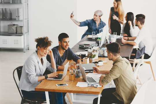 Friends and coworkers working together at open space in advertising agency
