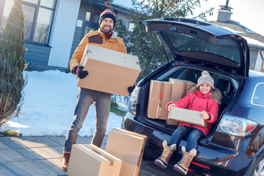 Moving to new apartment. Family together outdoors standing near car holding boxes smiling excited