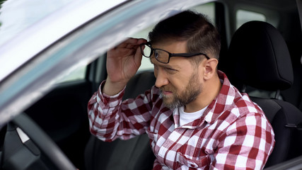 Tired driver taking eyeglasses off, eyesight disease, health weakness, health