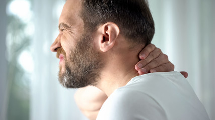 Caucasian male massaging neck, feeling discomfort, spinal problem, body care