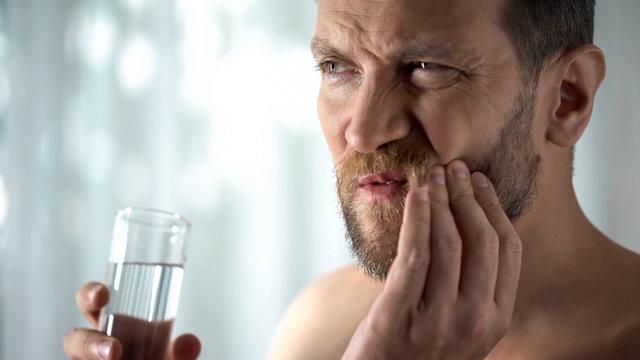 Man rinsing tooth with water, hypersensitivity, sharp dental pain, gingivitis