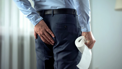 Office worker with toilet paper in hand suffering from hemorrhoid pain, diarrhea
