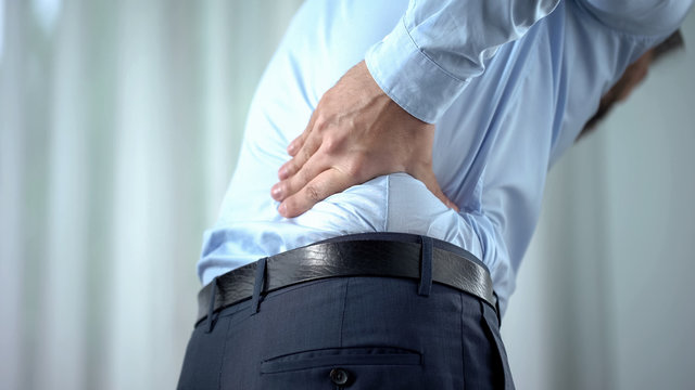 Male office worker feeling sharp back pain, sedentary lifestyle, slipped disc