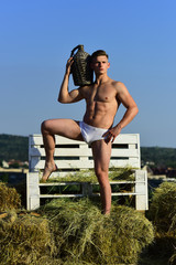 Good wine needs no bush. Athletic man with muscular body relax on summer day. A wine vintage is the year when grapes were harvested. Muscular man with bottle of vintage wine have summer fun