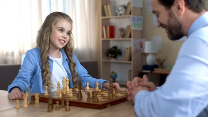 Cute girl smiling to father playing chess, first victory in game, family leisure